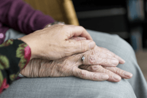 younger hand over elderly hands with wedding ring