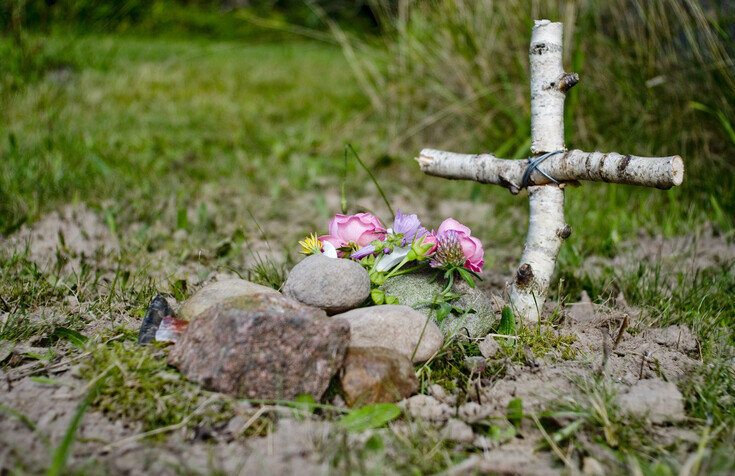 wooden cross next to pile of rocks and flowers
