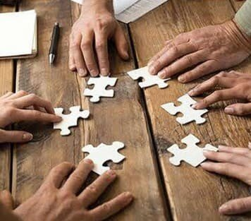 Different hands completing a puzzle